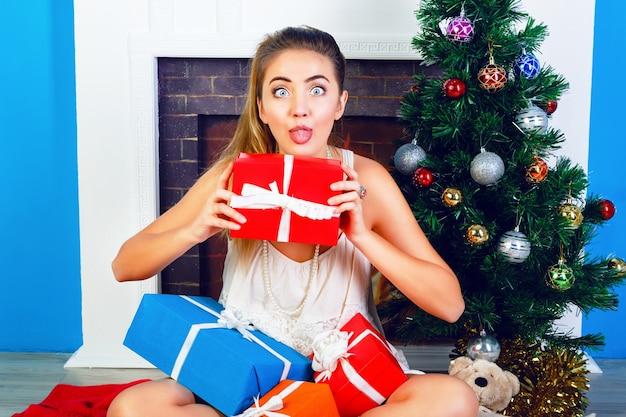 Kryty Jasny Portret śmieszne Młoda Blondynka Siedzi W Domu, W Pobliżu Drzewa Nowego Roku Darmowe Zdjęcia
