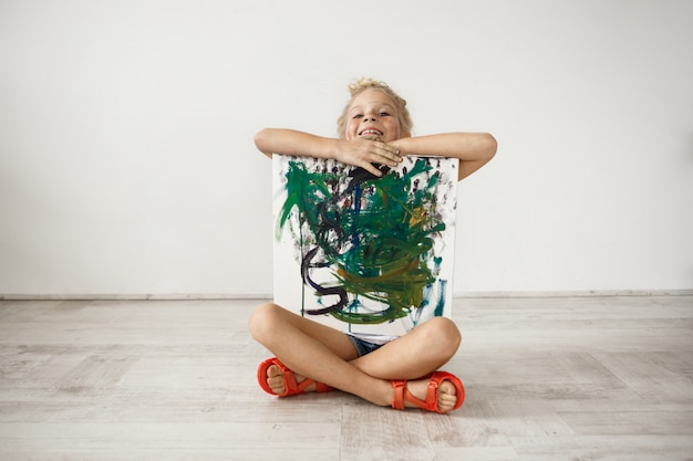 Kryty Portret Blondynki Uśmiechającej Się Zębami Dziewczynki Siedzącej Ze Skrzyżowanymi Nogami Na Podłodze, Przytulającej Obraz, Który Namalowała Dla Swoich Rodziców. Szczęśliwe Dziecko Jest Dumny Z Siebie. Ludzie I Postawa Darmowe Zdjęcia