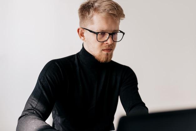 Kryty Portret Europejski Młody Człowiek Ubrany W Czarny Sweter I Okulary Do Pracy Z Laptopem W Lekkim Biurze W Słoneczny Dzień. Darmowe Zdjęcia