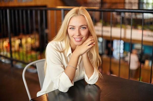 Kryty Portret Pięknej Młodej Blondynki Długowłosej Kobiety Pozującej Nad Wnętrzem Kawiarni, Patrząc Z Czarującym Uśmiechem I Opierając Głowę Na Skrzyżowanych Ramionach Darmowe Zdjęcia