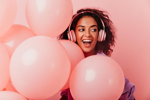 Kryty Portret Szczęśliwej Urodzinowej Dziewczyny Wyrażającej Pozytywne Emocje Na Pastelach. Zabawna Afrykańska Kobieta W Dużych Słuchawkach Pozuje Z Przyjemnością Obok Balonów. Darmowe Zdjęcia