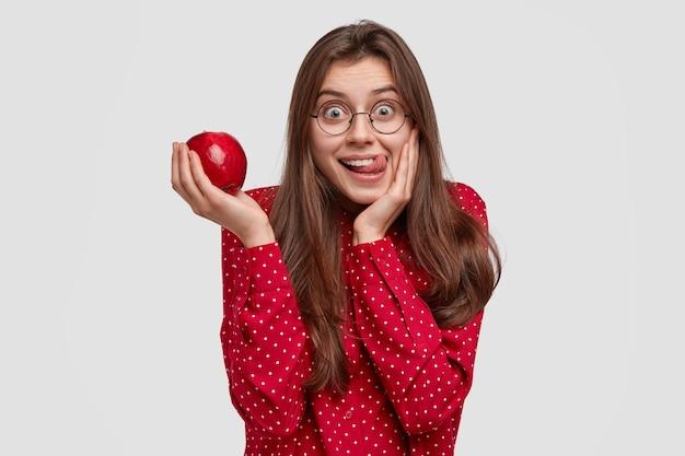 Kryty Strzał Atrakcyjnej Kobiety Oblizuje Usta, Trzymając świeże, Soczyste Jabłko, Bawi Się, Elegancko Ubrana, Lubi Jeść Witaminy Darmowe Zdjęcia