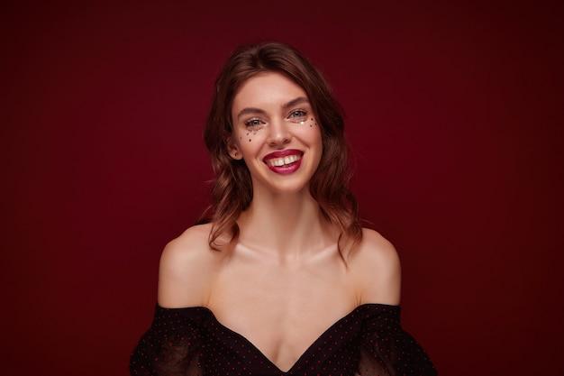 Kryty Strzał Atrakcyjnej Młodej Brązowowłosej Kobiety Z Falistą Fryzurą, Patrząc Radośnie I Demonstrując Jej Białe Idealne Zęby, Odizolowane Darmowe Zdjęcia