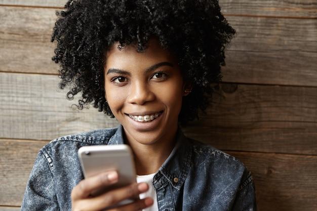 Kryty Strzał Piękna Szczęśliwa Afrykańska Dziewczyna Z Szelkami Patrząc I Uśmiechając Się Do Kamery Darmowe Zdjęcia