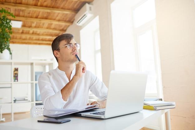 Kryty Strzał Zamyślony Skoncentrowany Młody Biznesmen Nosi Białą Koszulę W Biurze Darmowe Zdjęcia