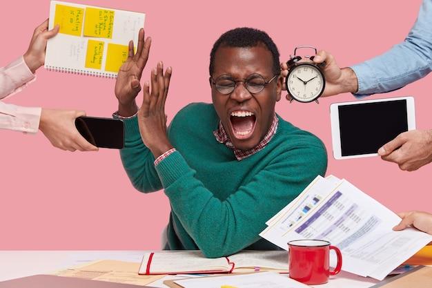 Kryty Strzał Zdesperowanego Młodego Mężczyzny Afro American Desperacko Krzyczy, Wykonuje Gest Stop, Ubrany W Zielony Sweter, Zajęty Pracą, Odizolowany Na Różowym Tle. Ludzie Darmowe Zdjęcia