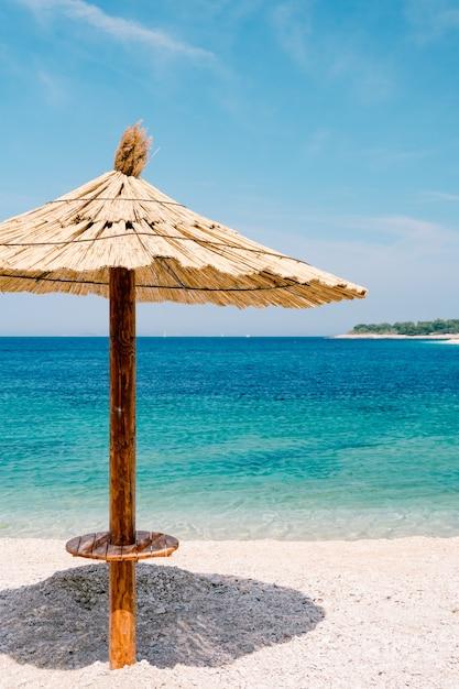 Kryty Strzechą Parasol Na Tle Błękitnego Nieba I Lazurowej Wody Na Piaszczystej Plaży Premium Zdjęcia