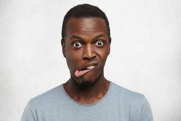Kryty Ujęcie Emocjonalnego Młodego Ciemnoskórego Mężczyzny W Szarym T-shircie, Wykrzywionego Grymasem I Wytrzeszczonymi Oczami Darmowe Zdjęcia