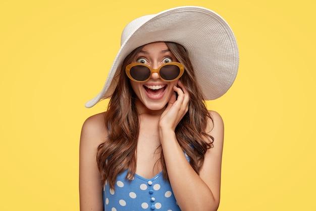 Kryty Ujęcie ładnie Wyglądającej Europejki Ma Przyjemny Uśmiech, Nosi Letnią Czapkę, Okulary Przeciwsłoneczne I Sukienkę, Ciesząc Się Z Niezapomnianej Podróży, Pozuje Nad żółtą ścianą. Koncepcja Mody Darmowe Zdjęcia