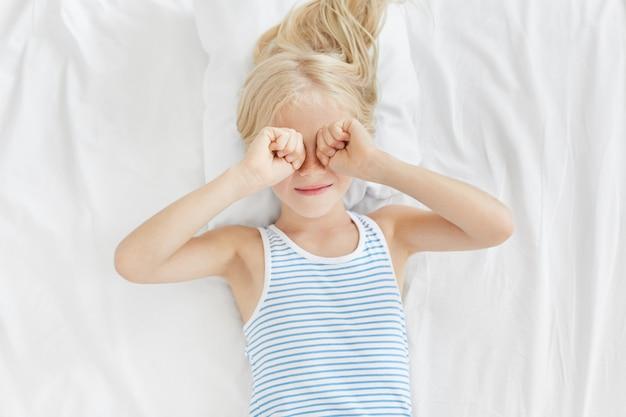 Kryty Ujęcie Małej Dziewczynki Przecierającej Oczy Rano Po Przebudzeniu, Leżącej Na Białej Pościeli I Chcącej Więcej Spać. śpiące Dziecko Leżące Na łóżku, Mające Zmęczoną Minę, Chcące Spać Darmowe Zdjęcia
