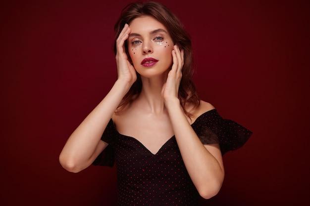 Kryty Ujęcie Młodej ładnej Kobiety Z Brązowymi Falującymi Włosami Delikatnie Dotykającymi Jej Twarzy I Wyglądającą Spokojnie, Ubrana W Elegancki Czarny Top W Czerwone Kropki Darmowe Zdjęcia