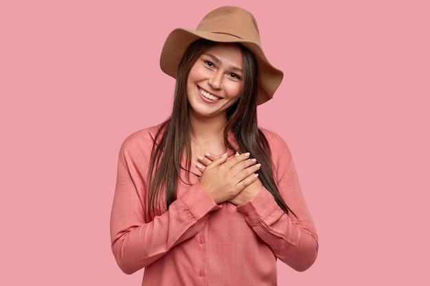 Kryty Ujęcie Przyjemnie Wyglądającej, Zadowolonej I Poruszonej Kobiety Ma Specyficzny Wygląd, Trzyma Obie Dłonie Na Sercu Darmowe Zdjęcia