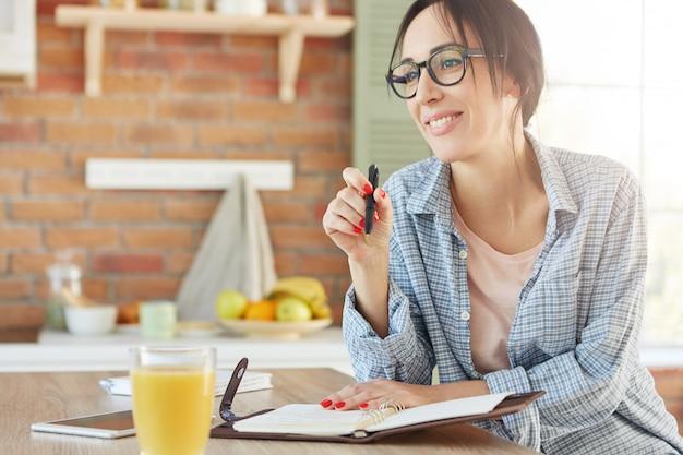 Kryty Ujęcie Uśmiechniętej Szczęśliwej Kobiety Siedzi Przy Kuchennym Stole, Robi Notatki W Dzienniku, Planuje, Co Robić, Darmowe Zdjęcia