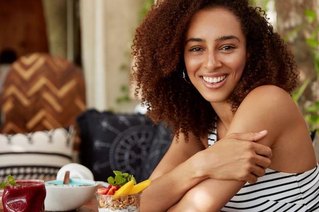Kryty Ujęcie Wesołej, Ciemnoskórej Afroamerykanki Młodej Kobiety O Radosnym Wyglądzie, Spędzającej Wolny Czas W Dobrym Towarzystwie, Siadającej Na Tle Wnętrza Kawiarni, Jedzącej Pyszne Desery. Koncepcja Rekreacji Darmowe Zdjęcia
