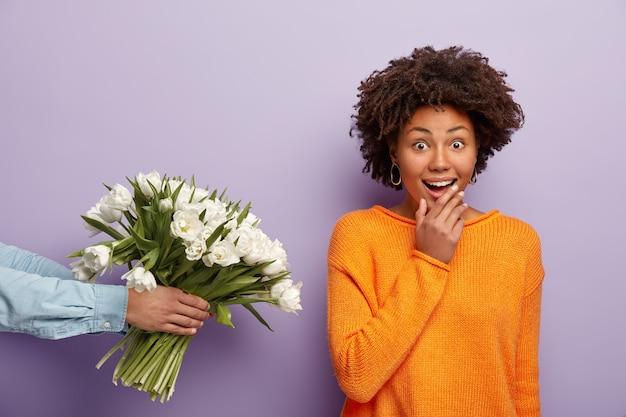 Kryty Ujęcie Wesołej, Zaskoczonej Ciemnoskórej Kobiety Otrzymującej Kwiaty Od Nieznajomego Darmowe Zdjęcia