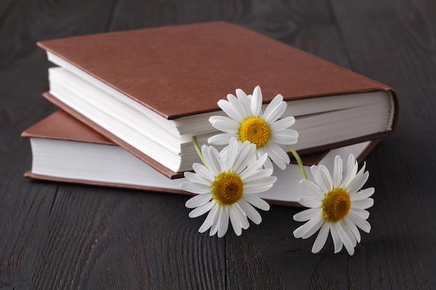 Książka I Stokrotka Kwiat Na Drewnianym Stole Premium Zdjęcia