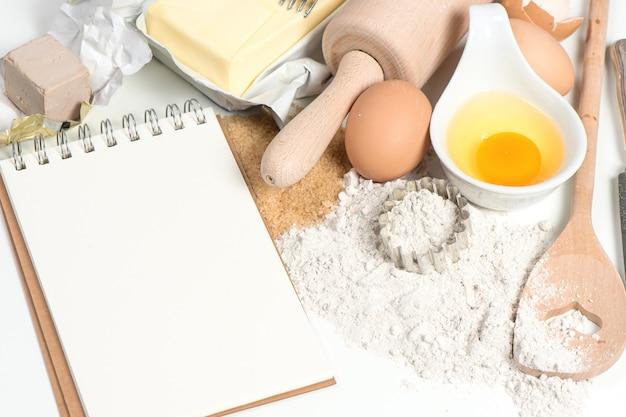 Książka kucharska i składniki do pieczenia jajka, mąka, cukier, masło, drożdże Premium Zdjęcia