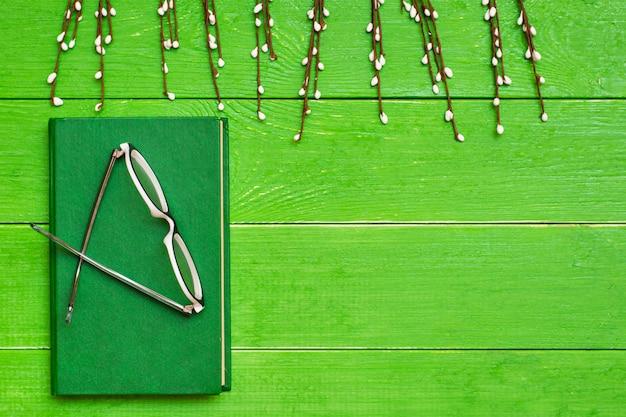 Książka w twardej zielonej okładce na zielonym drewnianym tle w okularach i branche wierzby Premium Zdjęcia