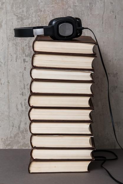 Książki audio, słuchawki na stosie książek Premium Zdjęcia
