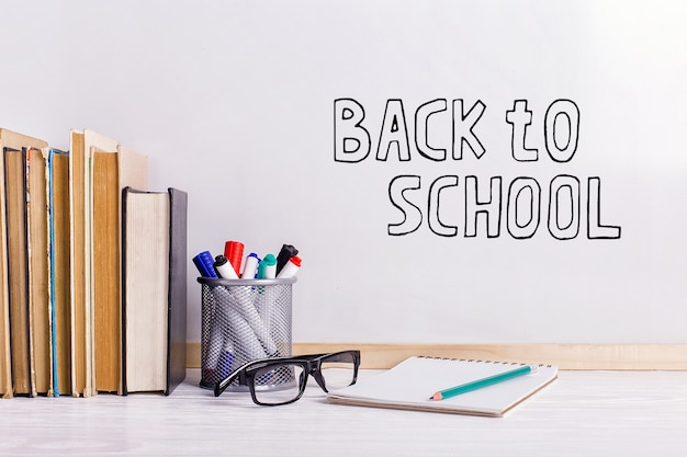 Książki, markery, notatnik, ołówek i szklanki na stole Premium Zdjęcia