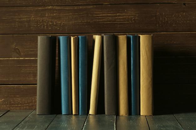 Książki zamykają up na starym drewnianym stole Premium Zdjęcia