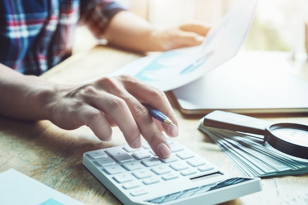 Księgowy naciska kalkulator, aby obliczyć dokładność budżetu inwestycyjnego Premium Zdjęcia