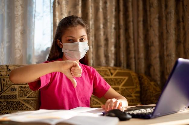 Kształcenie Na Odległość. Zakłopotana Młoda Dziewczyna W Masce Medycznej Siedząca W Domu, Pokazująca Kciuk W Dół, Nie Lubi Nauki Na Odległość Podczas Kwarantanny Koronawirusa Premium Zdjęcia