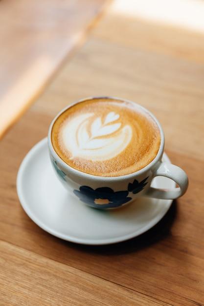 Kształt serca latte art podawany w ceramicznym kubku na drewnianym stole. Premium Zdjęcia
