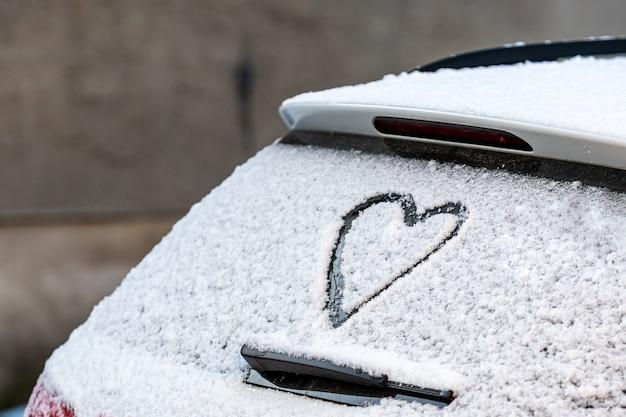 Kształt Serca Na Tylnym Oknie Samochodu Pokryte śniegiem Premium Zdjęcia