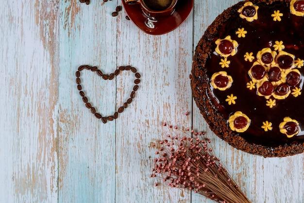 Kształt Serca Wykonany Z Ziaren Kawy Z Czekoladowym Ciastem Wiśniowym Premium Zdjęcia