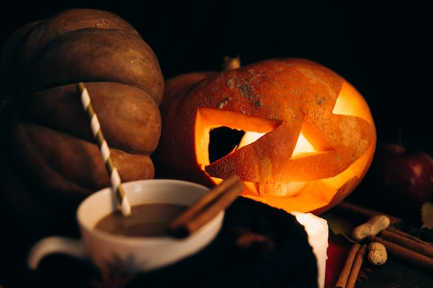Kubek Z Gorącą Czekoladą Stoi Przed Błyszczącą Scarry Halloween Dynia Darmowe Zdjęcia