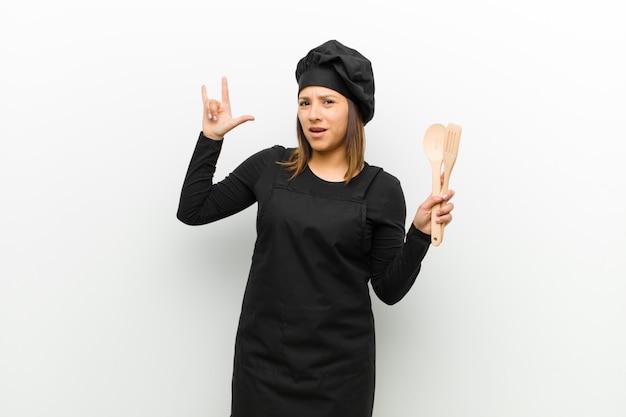 Kucbarska kobieta czuje się szczęśliwa, zabawna, pewna siebie, pozytywna i zbuntowana, robiąc znak rocka lub heavy metalu ręką na białym Premium Zdjęcia