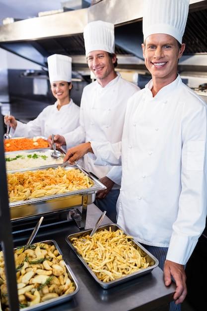 Kucharze stojący przy serwowaniu tac makaronu Premium Zdjęcia