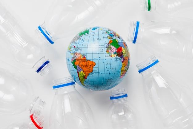 Kula ziemska otoczona plastikowymi butelkami na szarym stole Darmowe Zdjęcia