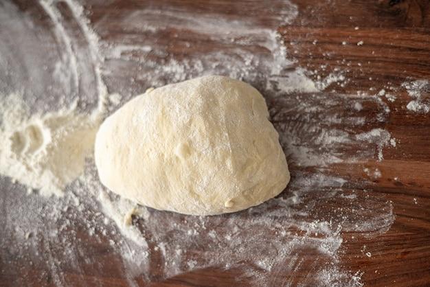 Kulka Ciasta Na Pizzę Na Rustykalnej Drewnianej Posypanej Mąką Mąki Premium Zdjęcia