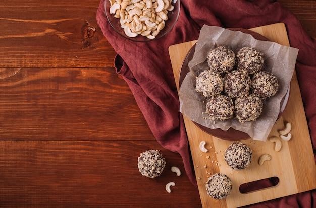 Kulki Kakaowe, Trufle Czekoladowe Ciasta Na Pokładzie Na Drewnianym Stole Premium Zdjęcia
