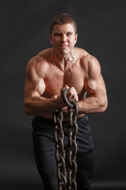 Kulturysta mężczyzna pozuje z żelaznym łańcuchem w jego rękach Premium Zdjęcia