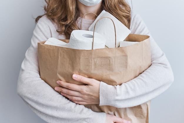 Kupowanie Paniki Na Kwarantannę Domową Z Powodu Koronawirusa. Zostań W Domu Dzięki Koncepcji Ochrony Covid-19. Kobieta Trzymać Torbę Na Zakupy Z Rolki Papieru Toaletowego Bibuły Premium Zdjęcia