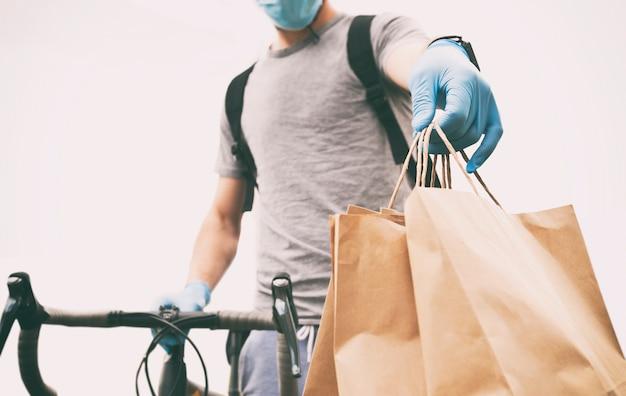 Kurier Na Rowerze Dostarcza Papierową Torbę Z Zamówieniem Do Osoby Premium Zdjęcia