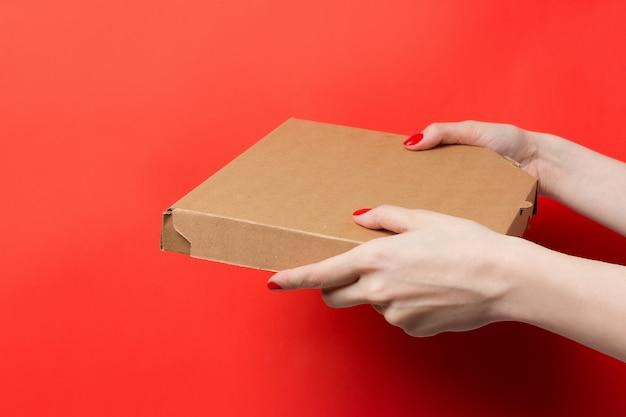 Kurier Trzyma Pizzy Pudełko W Rękach Odizolowywać Na Czerwonym Tle Premium Zdjęcia