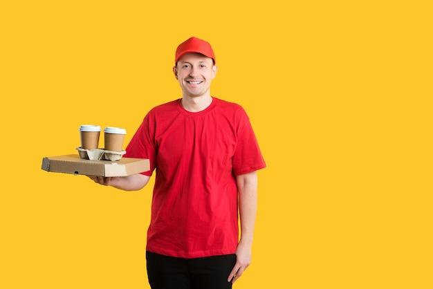 Kurier W Czerwonej Czapce I T-shirt Posiada Pudełka I Kawę Na żółto Premium Zdjęcia