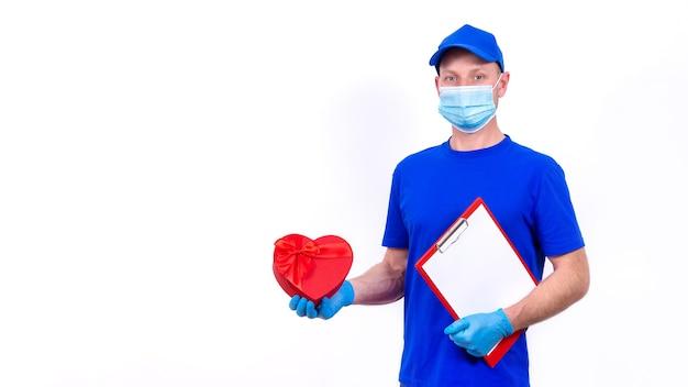 Kurier W Masce Ochronnej, Rękawiczki Trzyma Czerwone Pudełko W Kształcie Serca Na Walentynki. Premium Zdjęcia