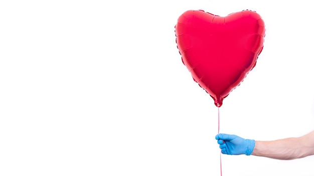 Kurier W Ochronnych Rękawiczkach Trzyma Balon W Kształcie Serduszka Na Walentynki. Premium Zdjęcia