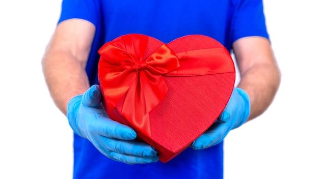 Kurier W Ochronnych Rękawiczkach Trzyma Czerwone Pudełko W Kształcie Serca Na Walentynki. Premium Zdjęcia