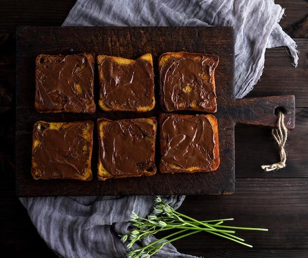 Kwadratowe Kawałki Smażonego Białego Chleba Rozmazane Czekoladą Premium Zdjęcia