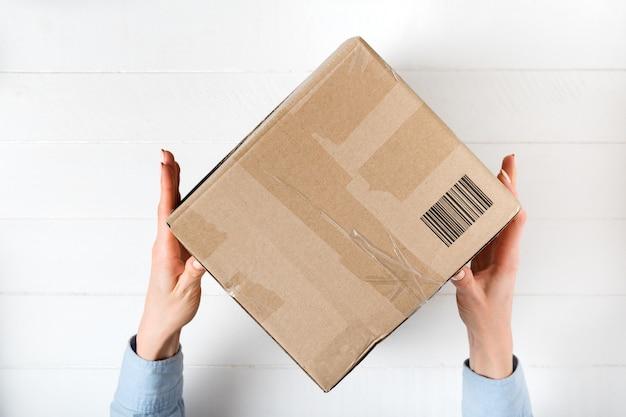 Kwadratowe Pudełko Kartonowe Z Kodem Kreskowym W Rękach Kobiet. Premium Zdjęcia