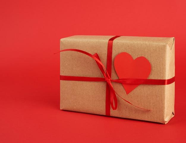 Kwadratowe Pudełko Owinięte Prezentem Z Brązowego Papieru Rzemieślniczego I Przewiązane Cienką Jedwabną Czerwoną Wstążką Premium Zdjęcia