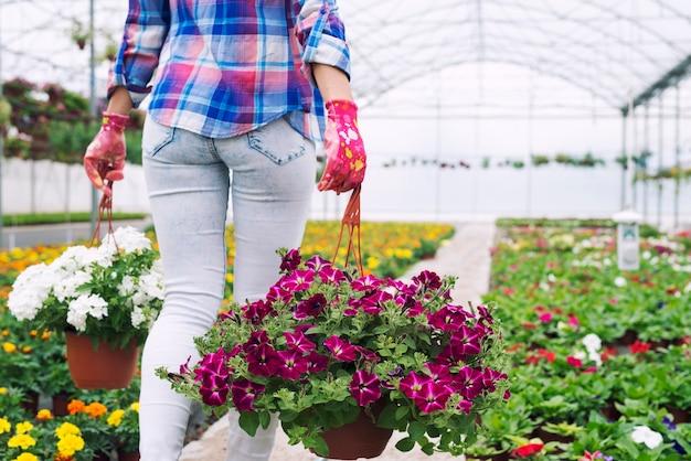 Kwiaciarnia Nie Do Poznania Kobieta Niosąca Doniczki I Kwiaty W Szkółce Roślin Darmowe Zdjęcia