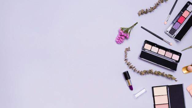 Kwiat i gałązki z pomadkami; pędzel do makijażu; szminka; kompaktowy proszek i paleta cieni do powiek na fioletowym tle Darmowe Zdjęcia