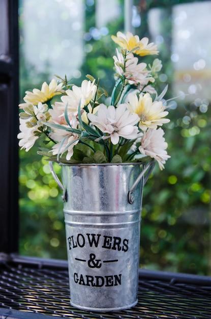 Kwiat W Aluminiowej Doniczce Na Czarnych Stalowych Półkach Premium Zdjęcia